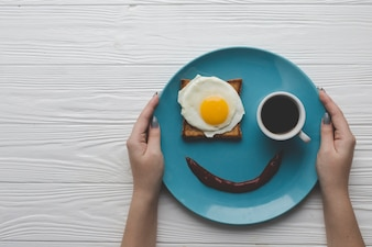 Crop hands holding plate with breakfast