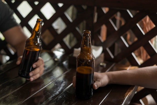 Crop hands keeping beer on table
