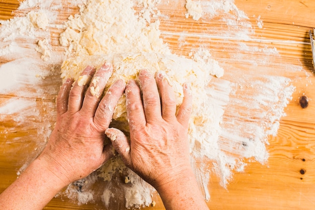Crop hands kneading dough