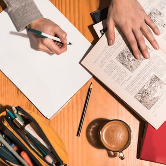 Crop hands making notes during studies