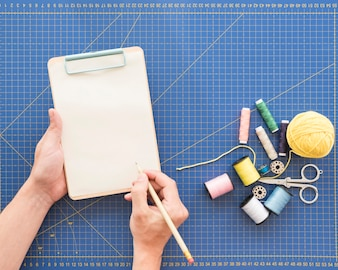 Crop hands making notes near sewing supplies