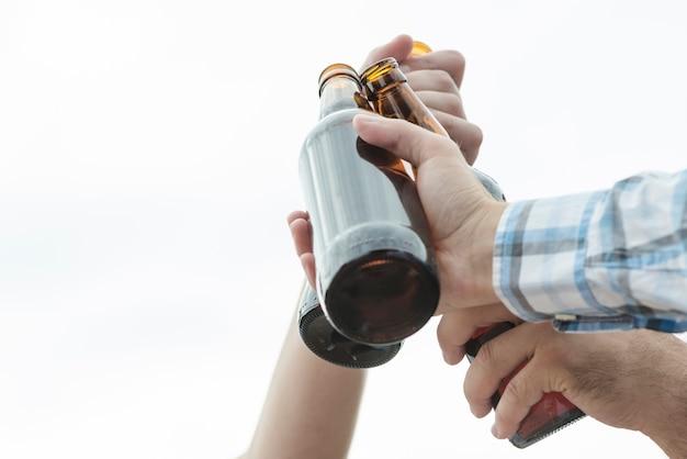 Crop hands of men clinking bottles of beer