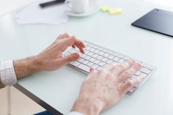 Crop hands near keyboard
