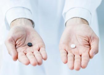 Crop hands offering two pills