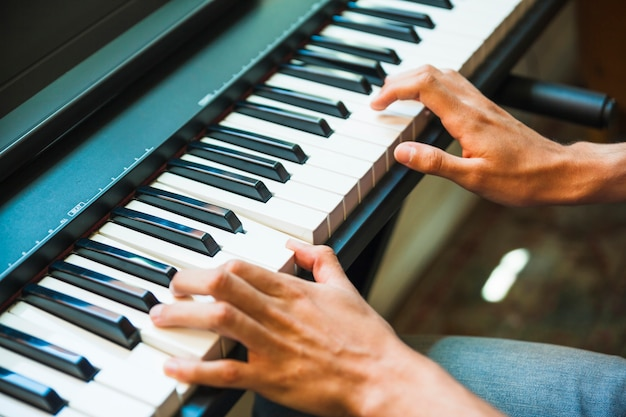 Crop hands playing electric piano