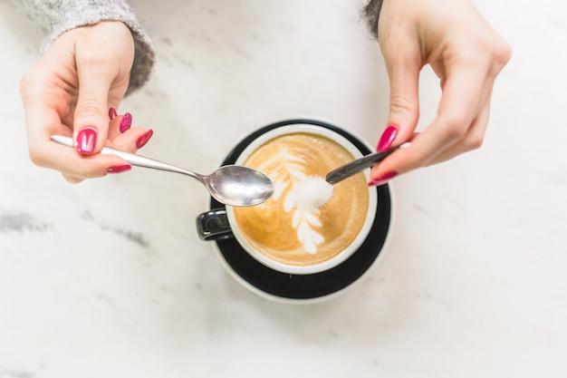 Crop hands pouring sugar into cappuccino cup