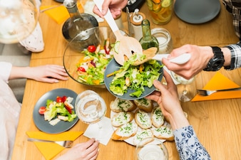 Crop hands putting delicious salad on plate