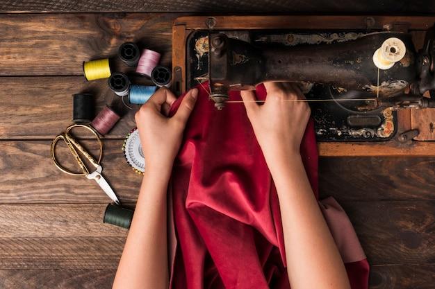 Crop hands sewing on machine