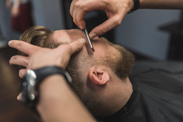 Crop hands shaving bearded man