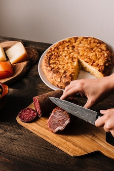 Crop hands slicing sausage near pie