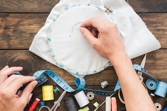 Crop hands stitching near sewing supplies