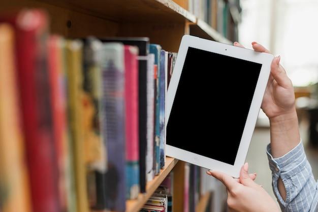 Crop hands taking modern tablet from shelf
