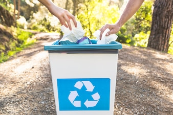 Crop hands throwinggarbage in bin in forest