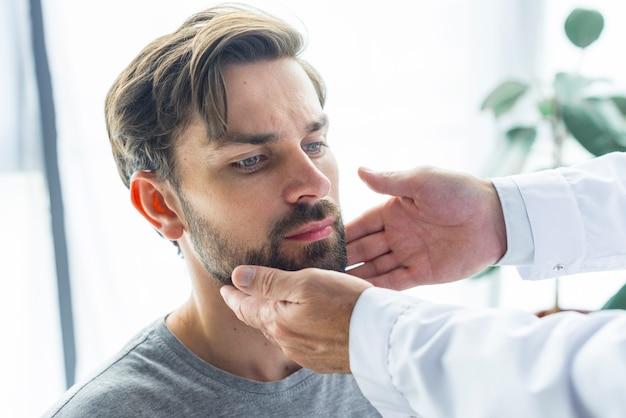 Crop hands touching lymph nodes of patient