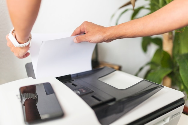 Crop hands touching paper in printer