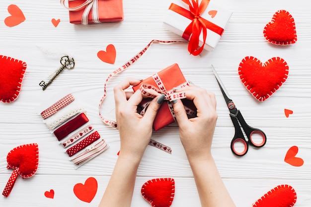 Crop hands tying ribbon on gift box