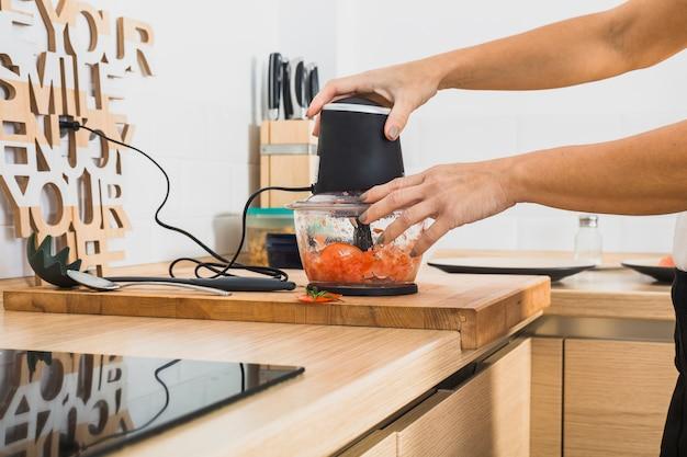 Crop hands using blender in kitchen