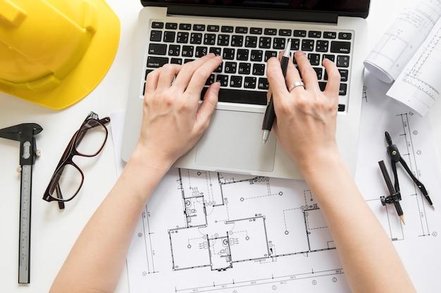 Ritaglia le mani usando il portatile vicino ai materiali da disegno