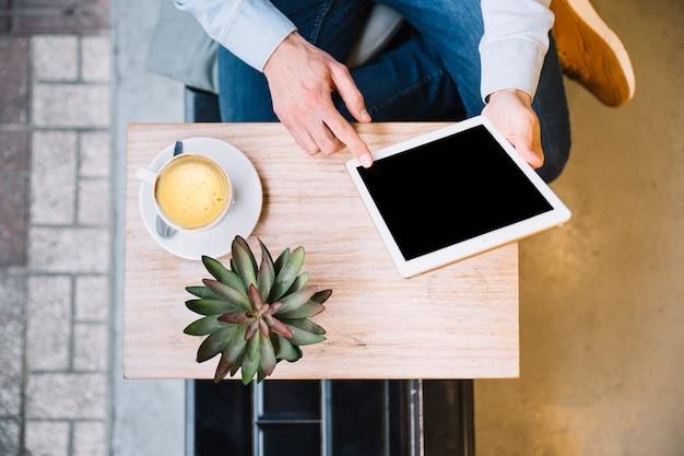Crop hands using tablet in minimalistic surroundings