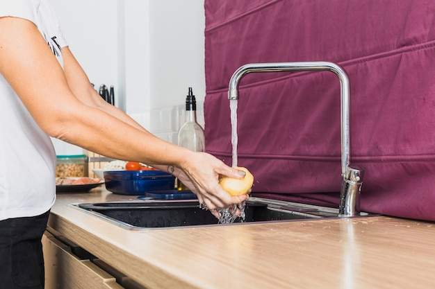 Crop hands washing raw potatoes in sink