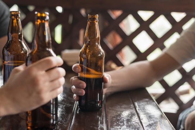 Crop hands with beer in pub