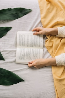 Crop hands with book on bed