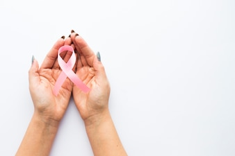 Crop hands with breast cancer ribbon