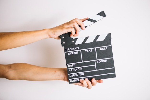 Crop hands with clapperboard