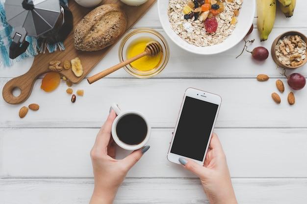 Обрезать руки с кофе и смартфоном Бесплатные Фотографии