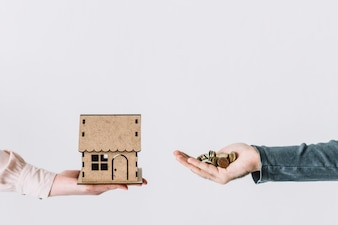 Crop hands with coins and house