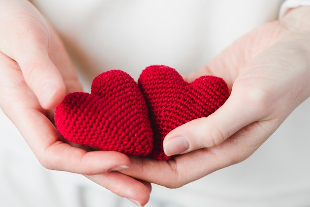 Crop hands with knitted hearts