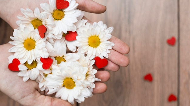 Crop hands with pile of flowers and hearts
