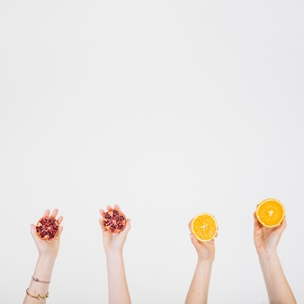 Crop hands with pomegranate and orange