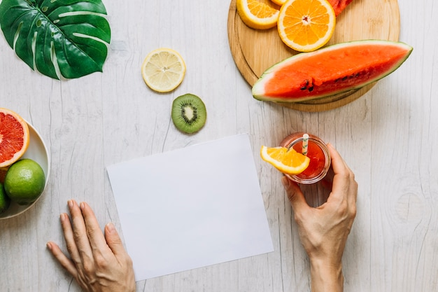 Crop hands with smoothie near fruits and paper sheet