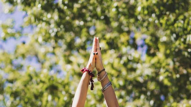 Crop hands of woman doing yoga