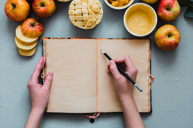 Crop hands writing near apples and pie