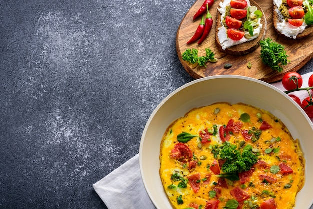 Crop healthy breakfast of omelet with cherry tomatoes and spinach in frying pan and toast with cottage cheese, pesto sauce and cherry tomatoes on black background.