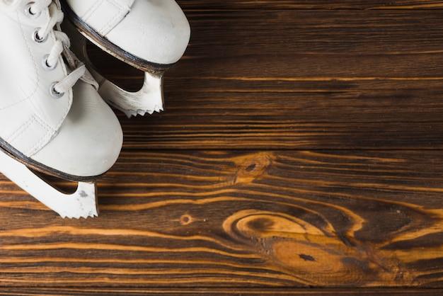 Raccolga i pattini da ghiaccio sul ripiano del tavolo di legno