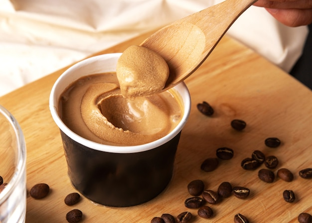 Crop image of hand scooping coffee ice cream in a paper cup with a wooden spoon