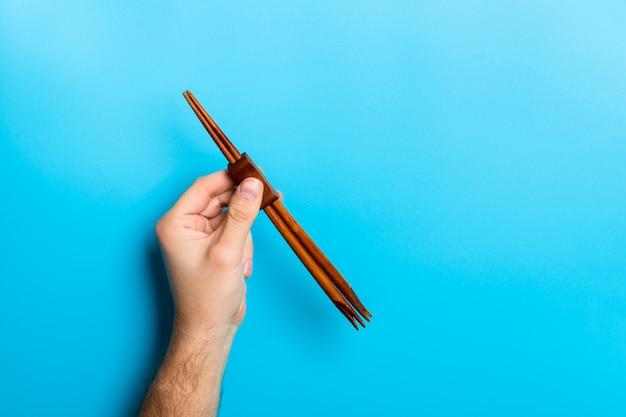 Crop image of male hand holding chopsticks