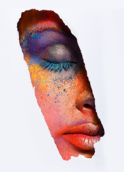 Обрезать изображение женского лица с закрытыми глазами с красочной пудрой. красивая фотомодель с креативным художественным макияжем. абстрактный красочный состав заставки. фестиваль холи