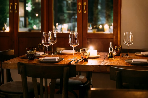 Crop image of romantic fine dining table with cutleries, plates, wine glasses, napkins and naperies on the table. light source from candle light.
