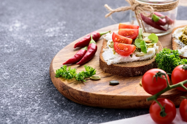 Crop image of toast with cottage cheese, pesto sauce, chili and cherry tomatoes on wooden board on black background