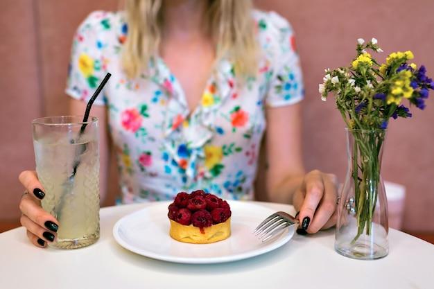 Ritaglia l'immagine della donna che mangia il dessert al lampone al ristorante, tenendo una grande limonata dolce, indossando abiti floreali, sfondo rosa, colori pastello