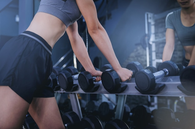 Crop image of woman muscular bodybuilder workout with dumbbells choosing her weight in fitness gym.