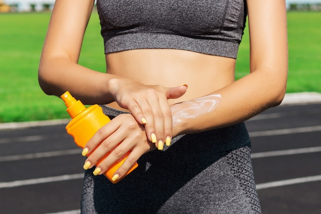Crop image of a woman protecting her hands and arms with sunblock before training at the stadium on a sunny day.