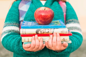 Crop kid with books and apple