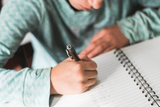 Crop kid writing in notebook