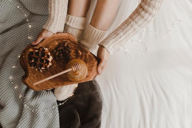ワッフルとハチミツを保持する作物の女性