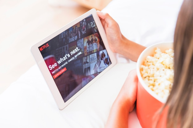 Crop lady with popcorn looking at netflix site